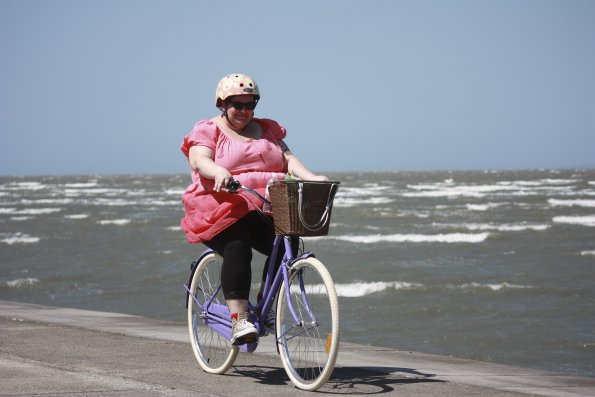 A fat woman cycling on a beach.