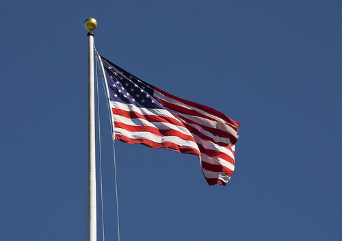 A US flag waving in a breeze on a clear day.
