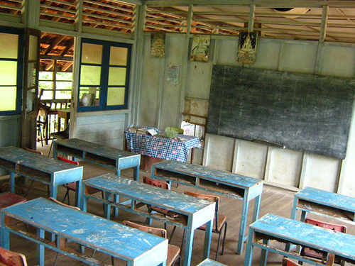 A classroom in Indonesia with worn desks and a stark look.