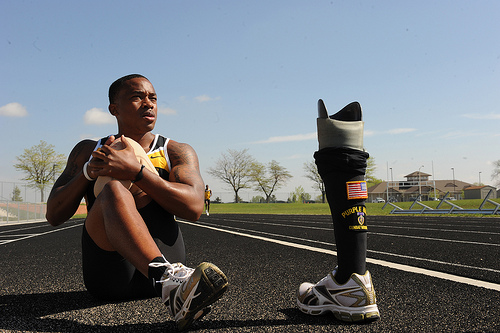 An amputee resting on a track, with his prosthetic leg off.