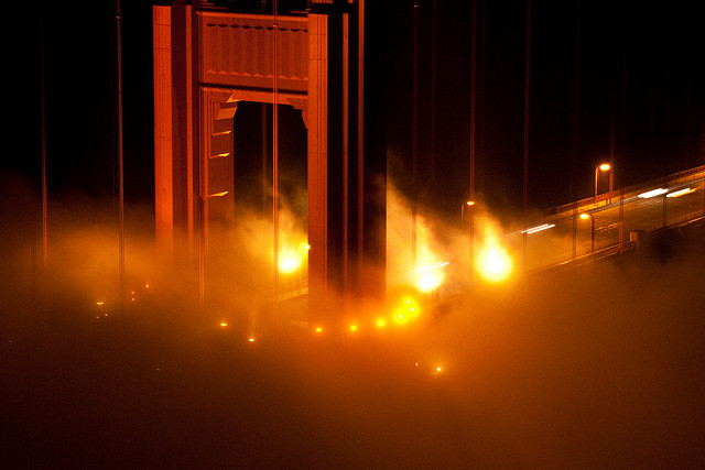 A shot of the Golden Gate Bridge at night, wreathed in low-lying fog.