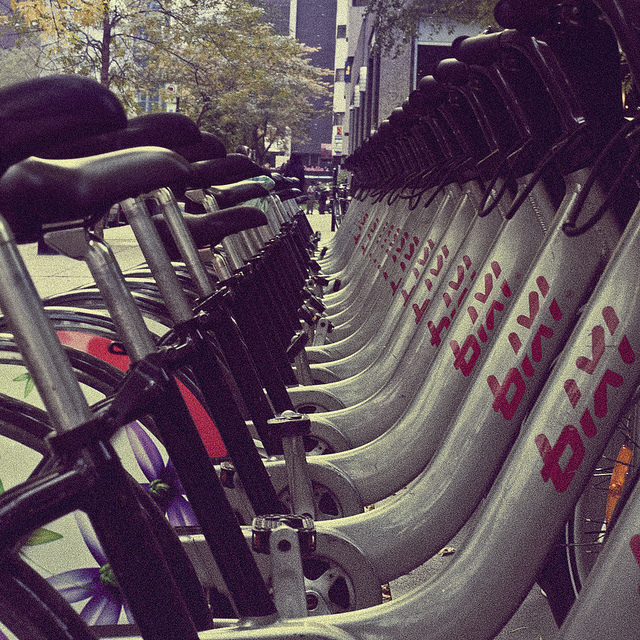 A row of bicycles ready for use at a bike sharing station.