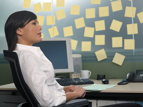 A rather hilarious stock photo of a woman seated at a computer with post-it notes all over the wall of her office.