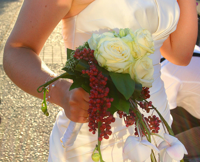 A bride walking with her bouquet in golden light.