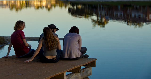 A group of teens sitting on a dock at dusk.