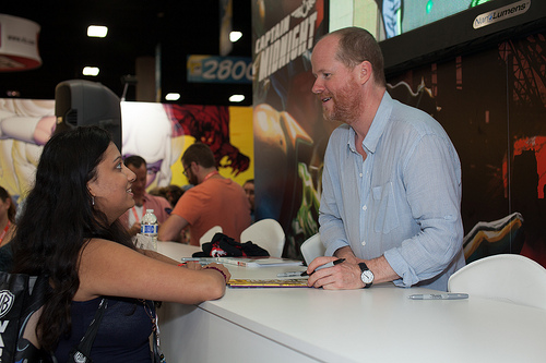 Joss Whedon at a signing table with a fan.