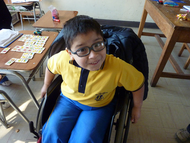 A young child with large glasses seated in a wheelchair, looking up at the camera.