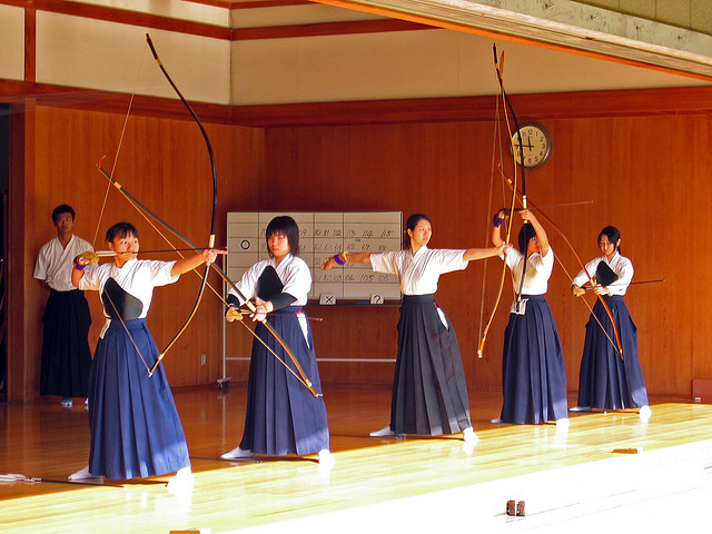 Japanese women in training gear practicing with bows in a martial arts studio.