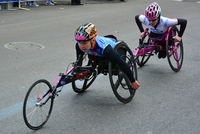 Two wheelchair racers approaching the finish line.