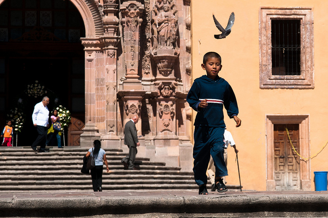 A young boy walking away from a Spanish-style building.