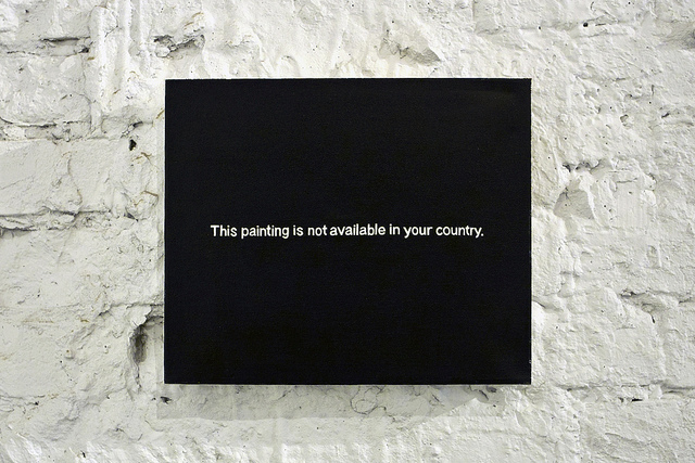 A painting hanging on a brick wall. The painting is black, with the words THIS PAINTING IS NOT AVAILABLE IN YOUR COUNTRY written across it.