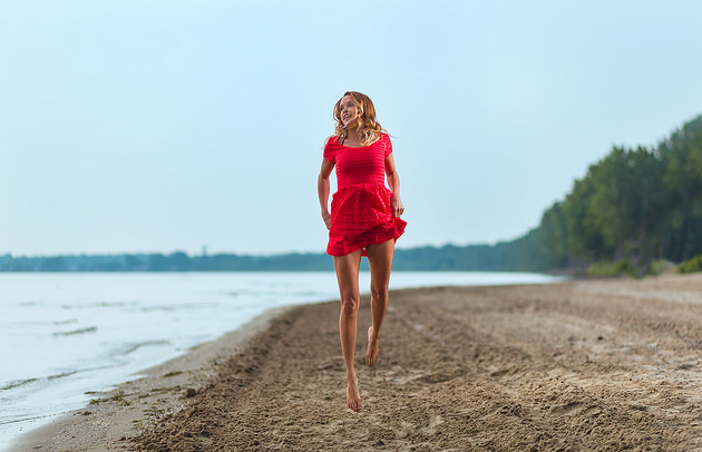 A woman in a red dress jumping in the air on a beach.