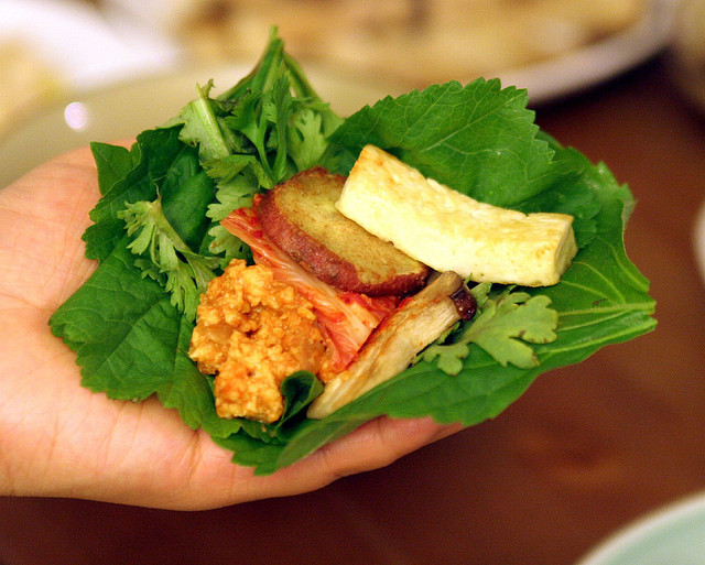 An outreached hand with a leaf, covered with tasty vegan fillings.