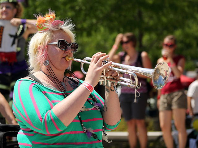 A fat person in a green shirt blowing a trumpet.