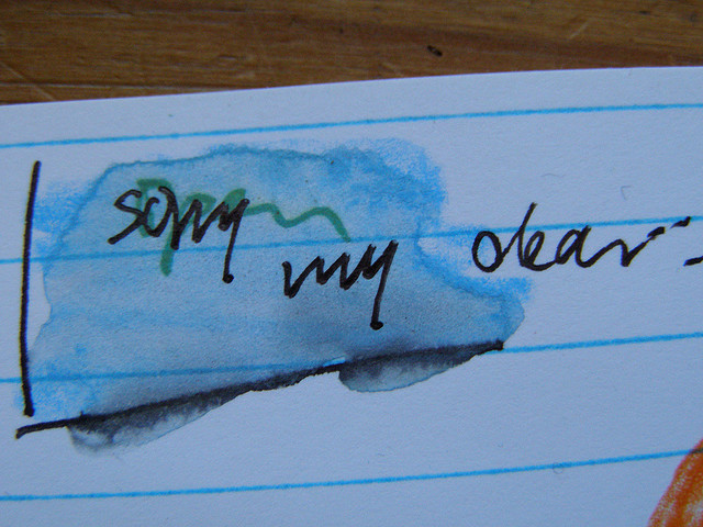 The words SORRY MY DEAR written on notebook paper, stained with water and smeaing