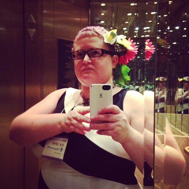 The author in a mirrored elevator, holding up a phone to take a selfie.