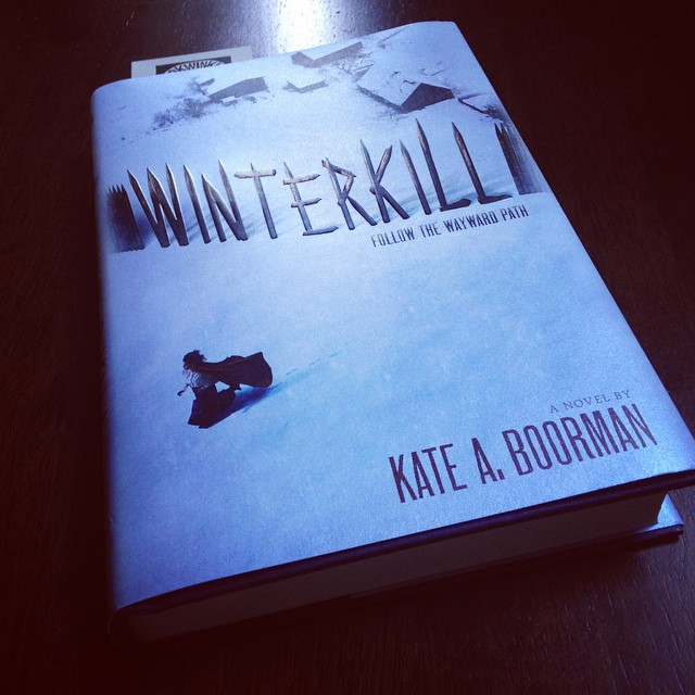 My copy of WINTERKILL on the table. The book's cover shows a snowy scene with a stockade fence, and a cloaked woman running away.
