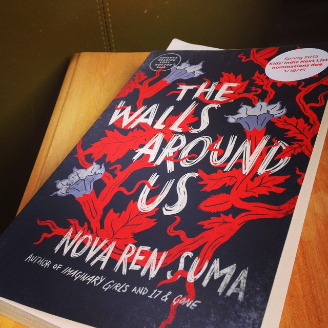 My copy of THE WALLS AROUND US, a book with tangled red and purple vines on the cover.