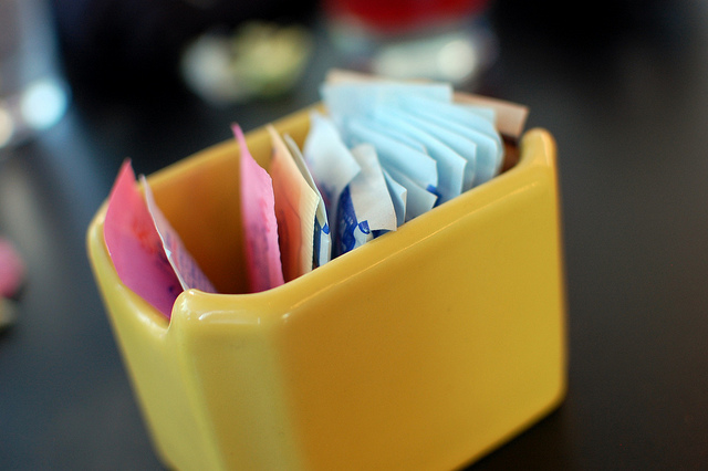 An array of sweeteners in a dish at a diner