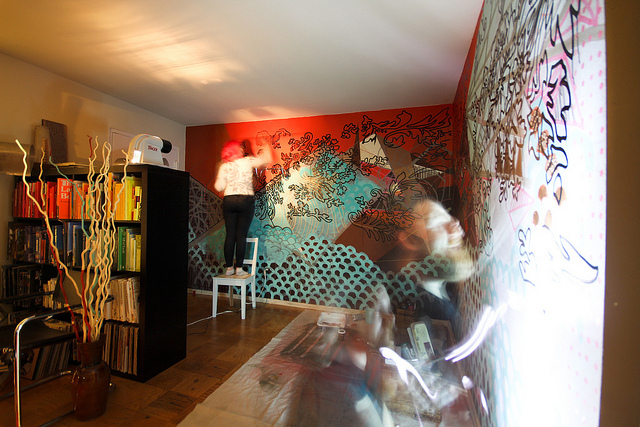 A room with walls covered in murals and art with people swirling around it