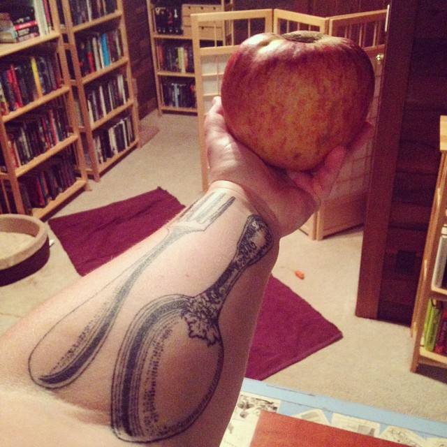 Me stretching out my tattooed arm while I hold an apple.