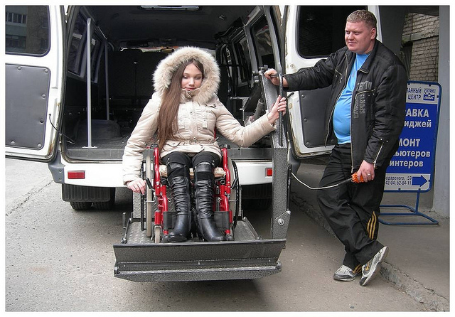 A wheelchair user getting out of a van