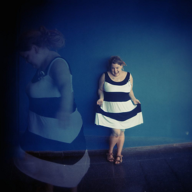 A fat person wearing a striped dress in a double exposure showing the dress from the front and side