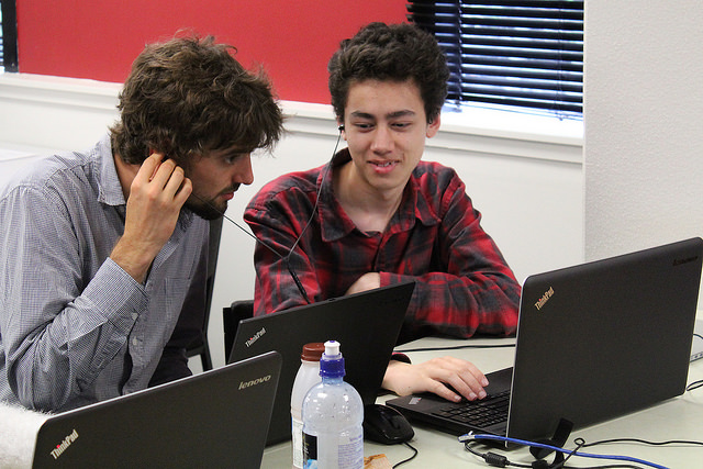 Two programmers studying a computer while they discuss accessibility
