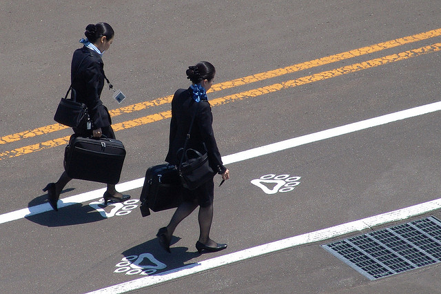 Two flight attendants walking on the tarmac