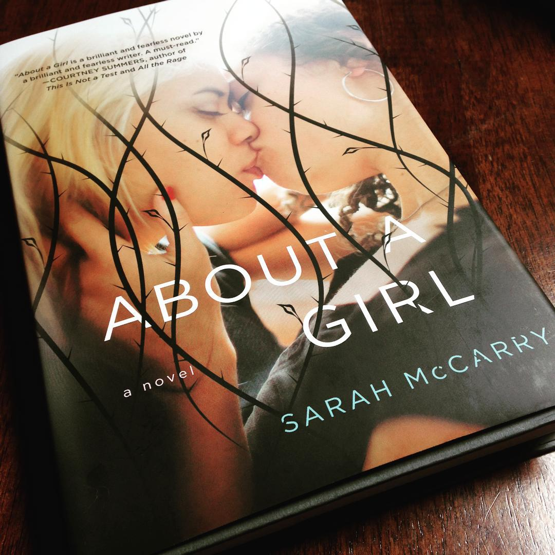 Two girls kissing on the cover of ABOUT A GIRL
