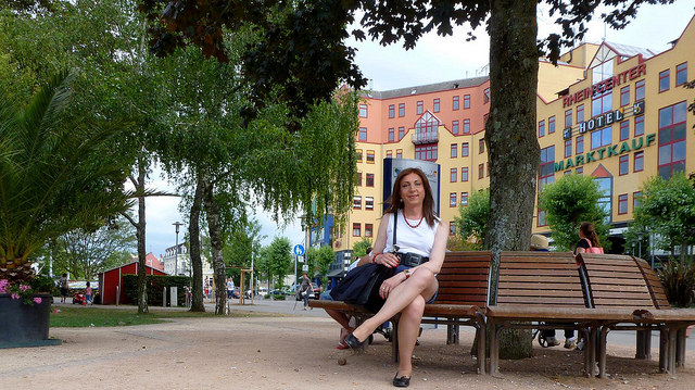 A trans woman sitting on a bench