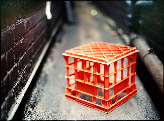A red milk crate upended in an alley.