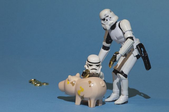 Two Stormtroopers putting money in a piggybank.