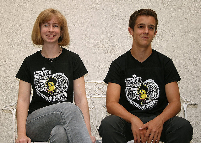 Two people wearing shirts advertising the fact that they're dying for kidneys