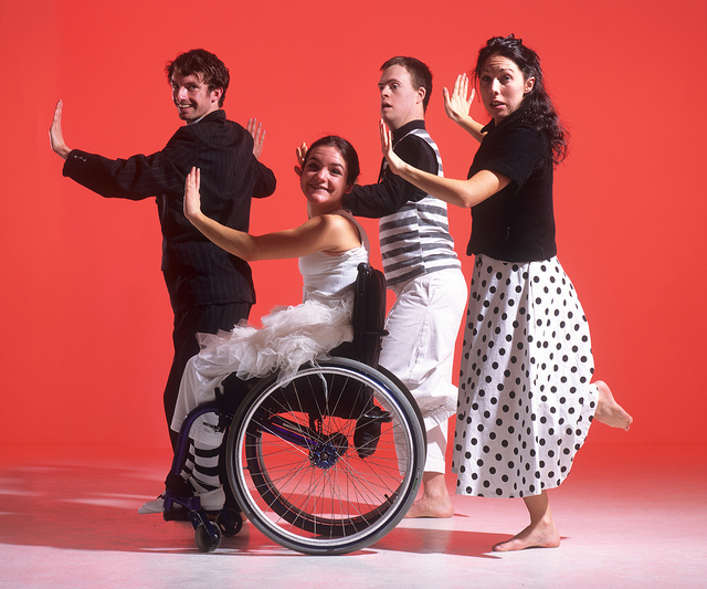 Four dancers, one of whom is using a wheelchair, against a red background.