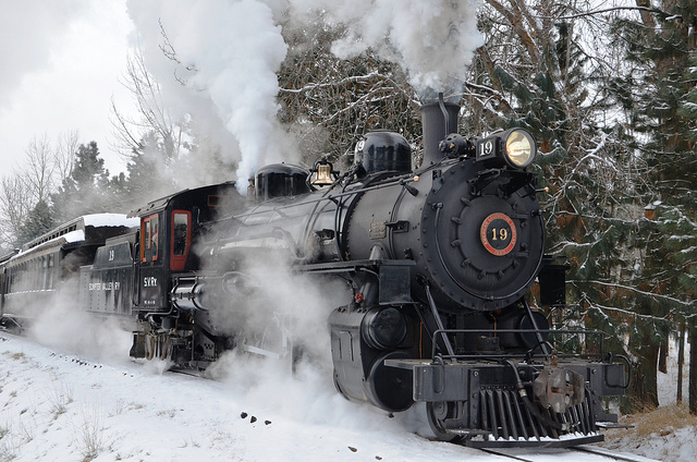 A restored steam train chuffing in the snow.