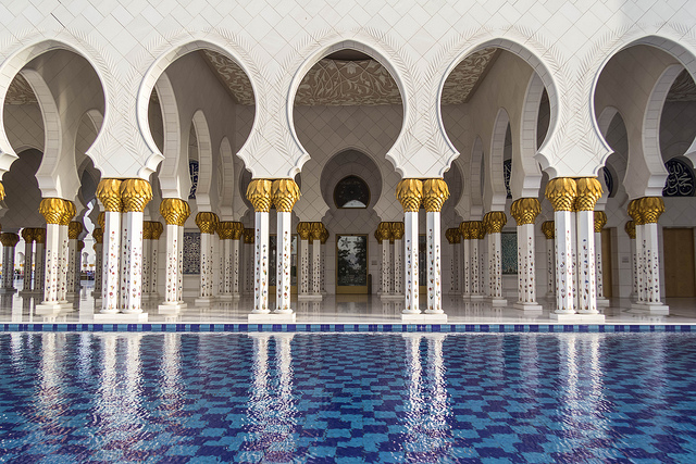 The colonnade of a beautiful mosque, columns reflected in a stunning pool.