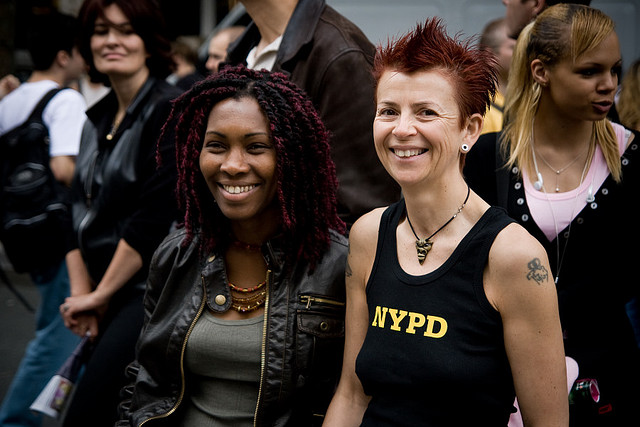 A biracial lesbian couple smiling at Pride.