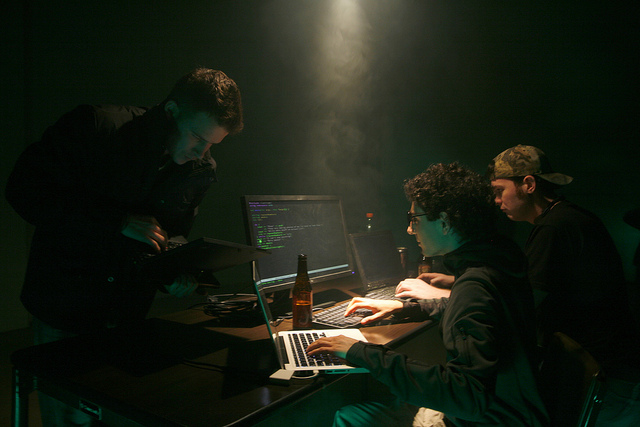 Three people posing around a computer screen in a darkened room.