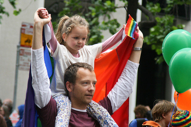 A toddler sitting on a person's shoulders during a parade.