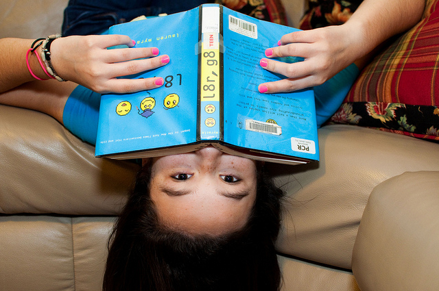 A young person dangling upside-down on a couch with a book in hand.