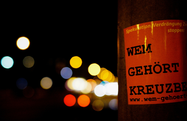A sticker in German slapped across a light pole.