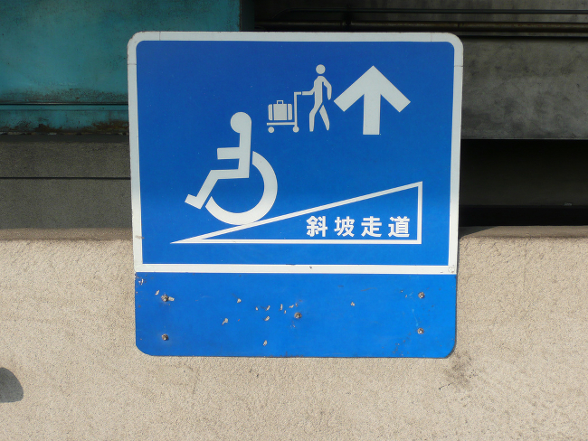 A sign pointing the way towards a wheelchair ramp