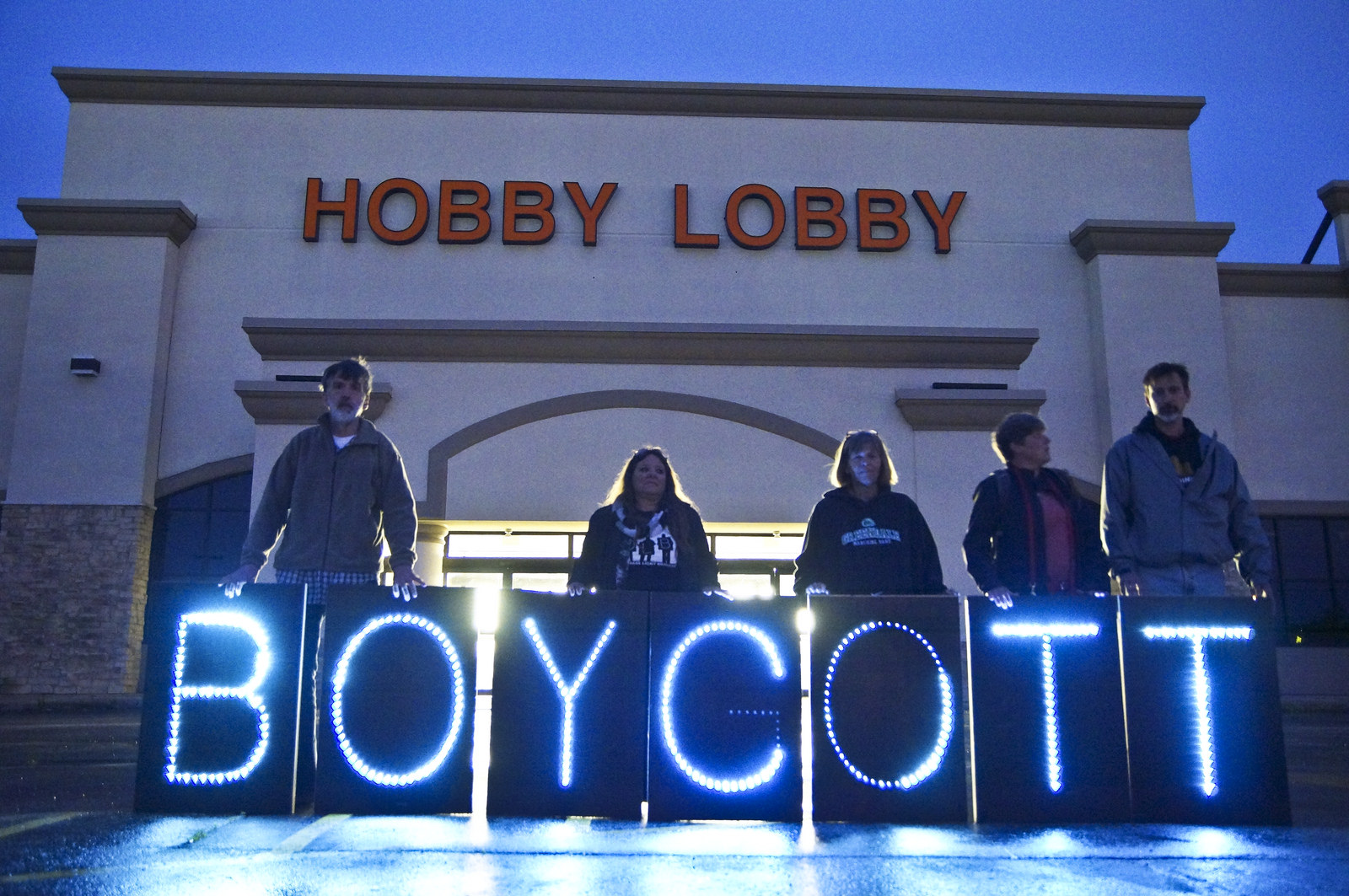 People standing in front of a Hobby Lobby store with boycott signs