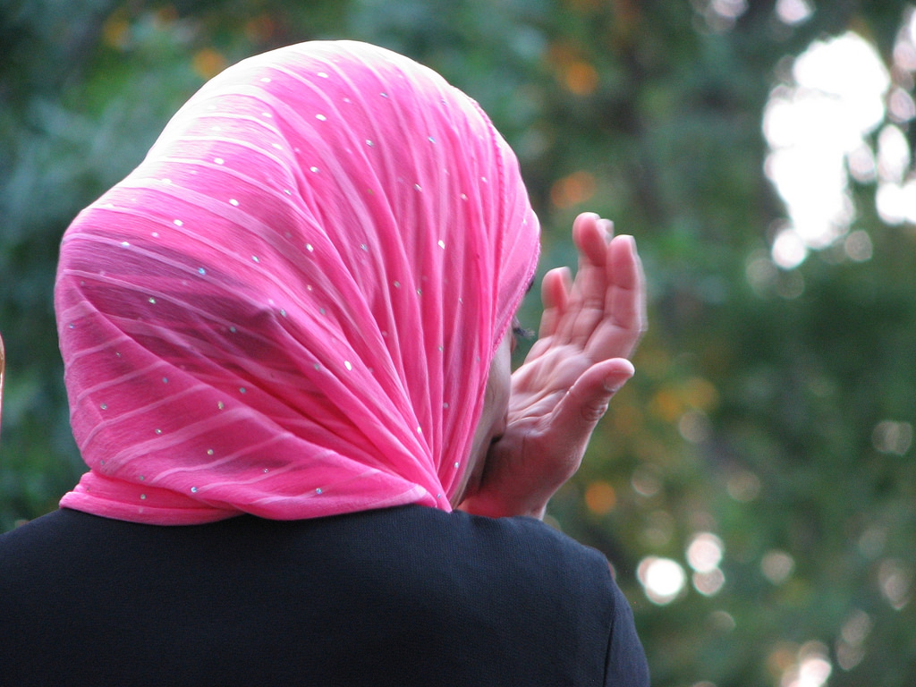 A person wearing a pink hijab, turned away from the camera.