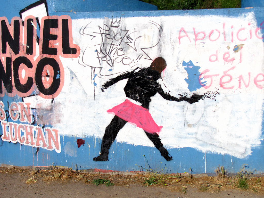 Street art of a black figure in a pink skirt throwing an object that's a bit hard to discern in this photo honestly