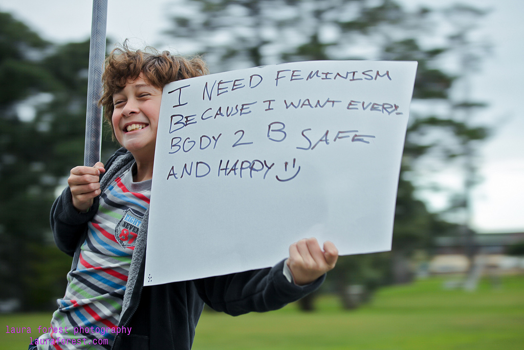 A young person grinning and holding up a sign explaining that they need feminism because they want everybody to be safe and happy.