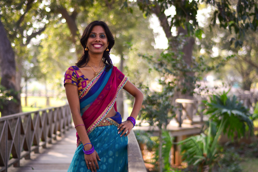 A Desi girl wearing a saree and smiling