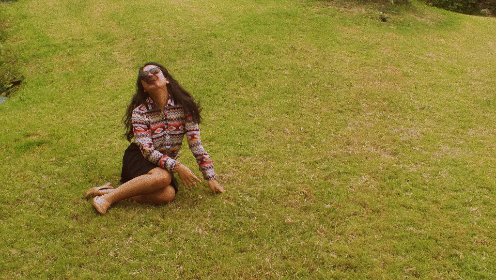 A girl lying in the grass and laughing.