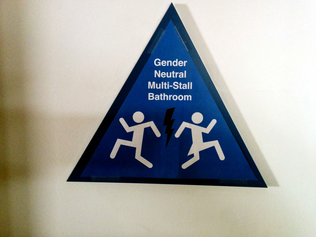 A multistall bathroom with a sign indicating that it is available to all genders.